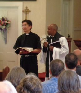 Asia meets Africa at Light of Christ, Portland: Pastor Abraham Chan translates into Mandarin for preacher, Fr. Jean Ngabo Segasinde.